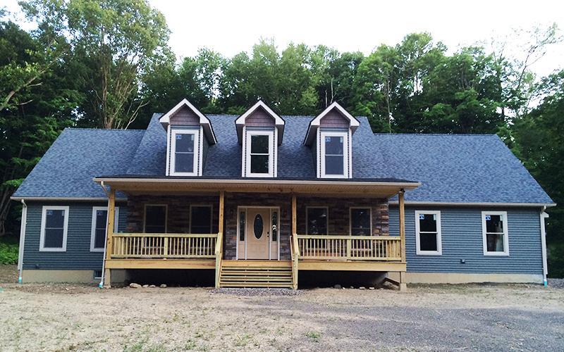 3 Dormer House with Stone Facade and Green Siding